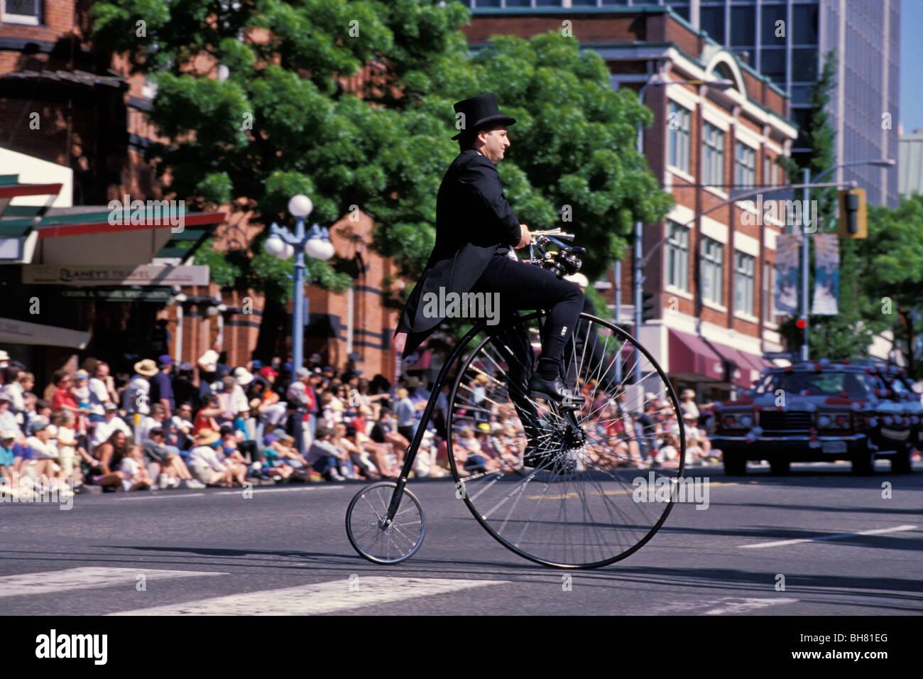 Man riding velocipede bicycle, Victoria Day parade, Victoria, British Columbia, Canada - Stock Image