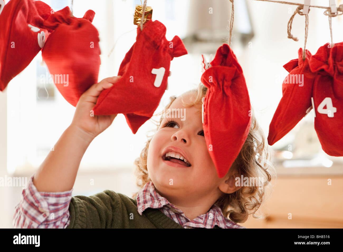 Young boy inspecting christmas sacks - Stock Image
