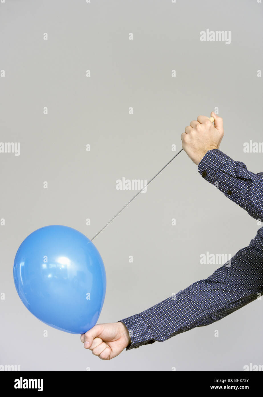 men's hands about to burst a balloon - Stock Image