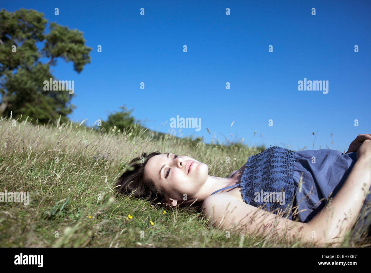 Woman relaxing on hill Stock Photo