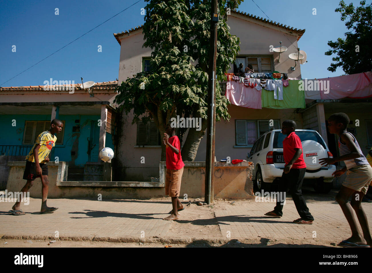 Children play football on a sidewalk in Menongue, Angola, Africa. - Stock Image