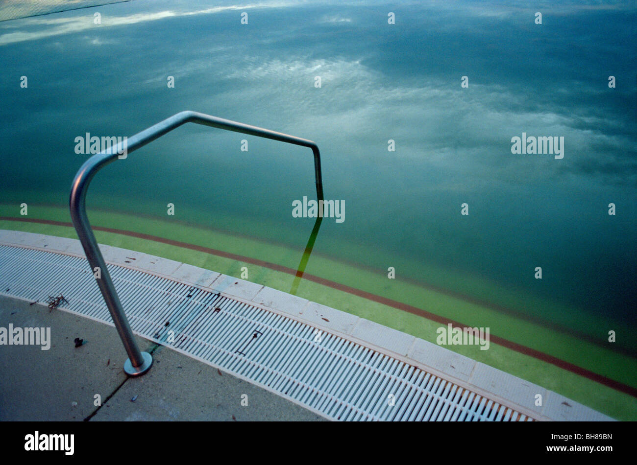 Edge of a murky swimming pool - Stock Image
