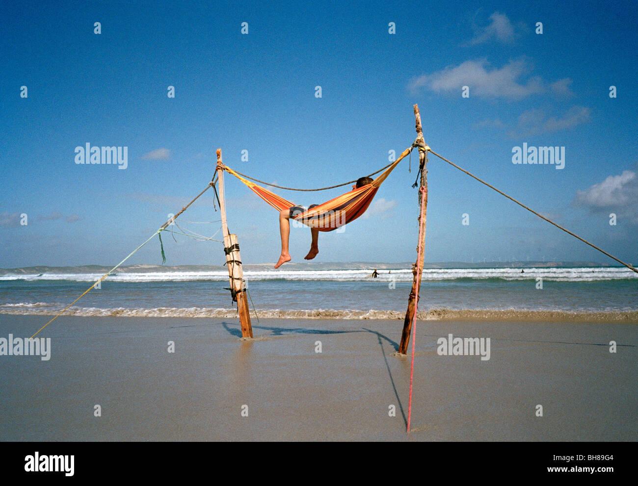 A man lying in a hammock on a beach - Stock Image