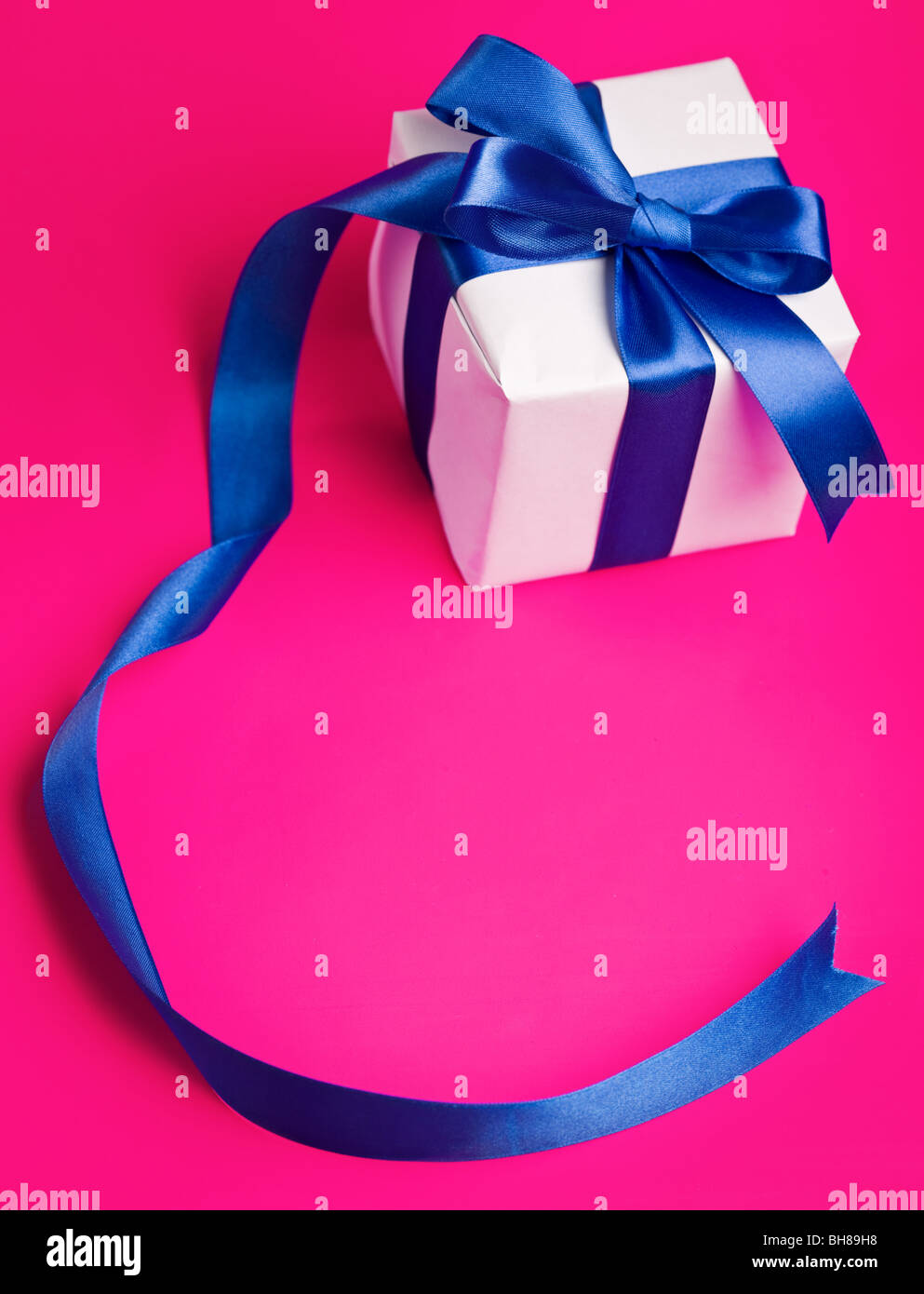 white gift in a blue ribbon on a pink background - Stock Image