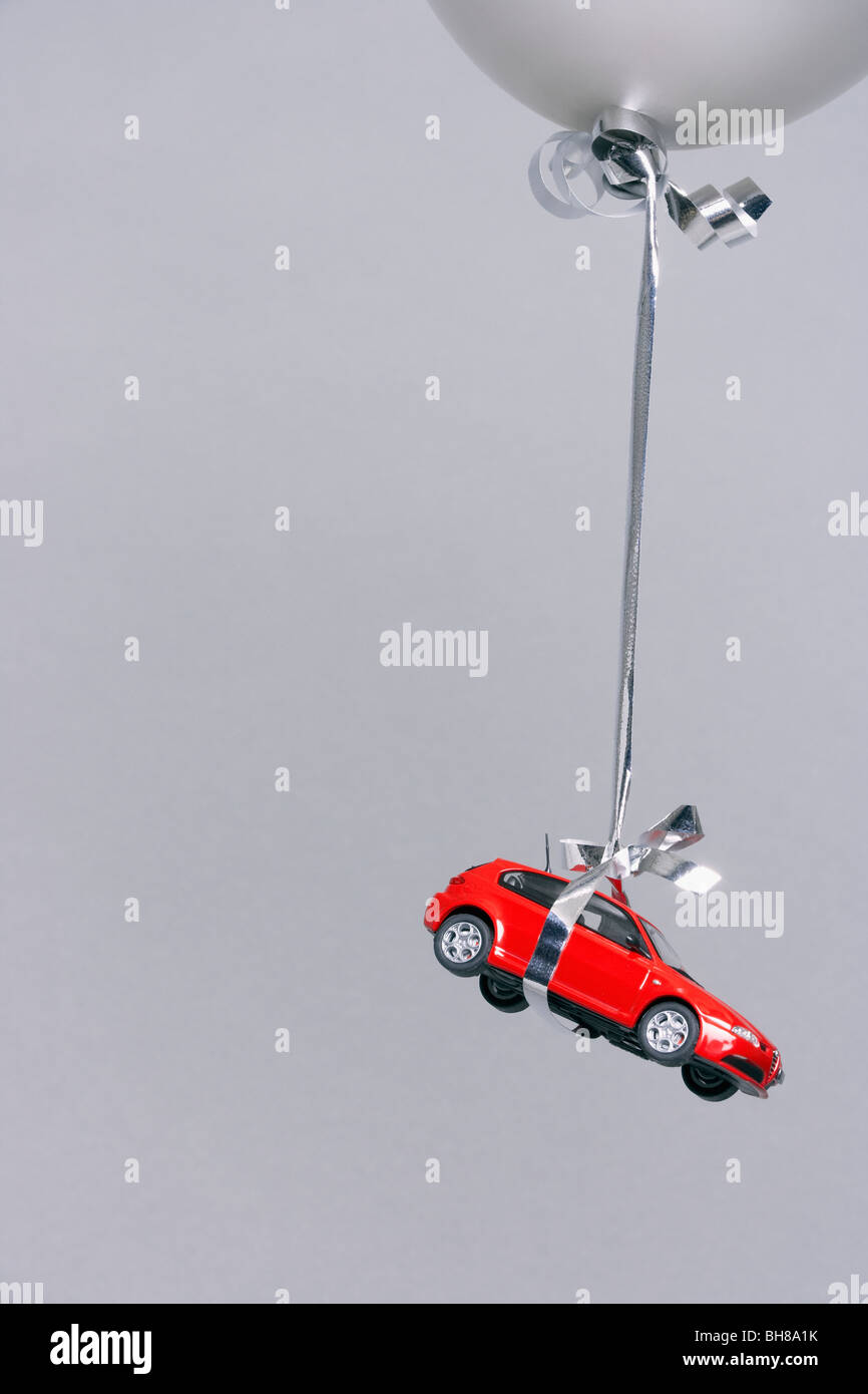 Red car carried by a grey balloon - Stock Image