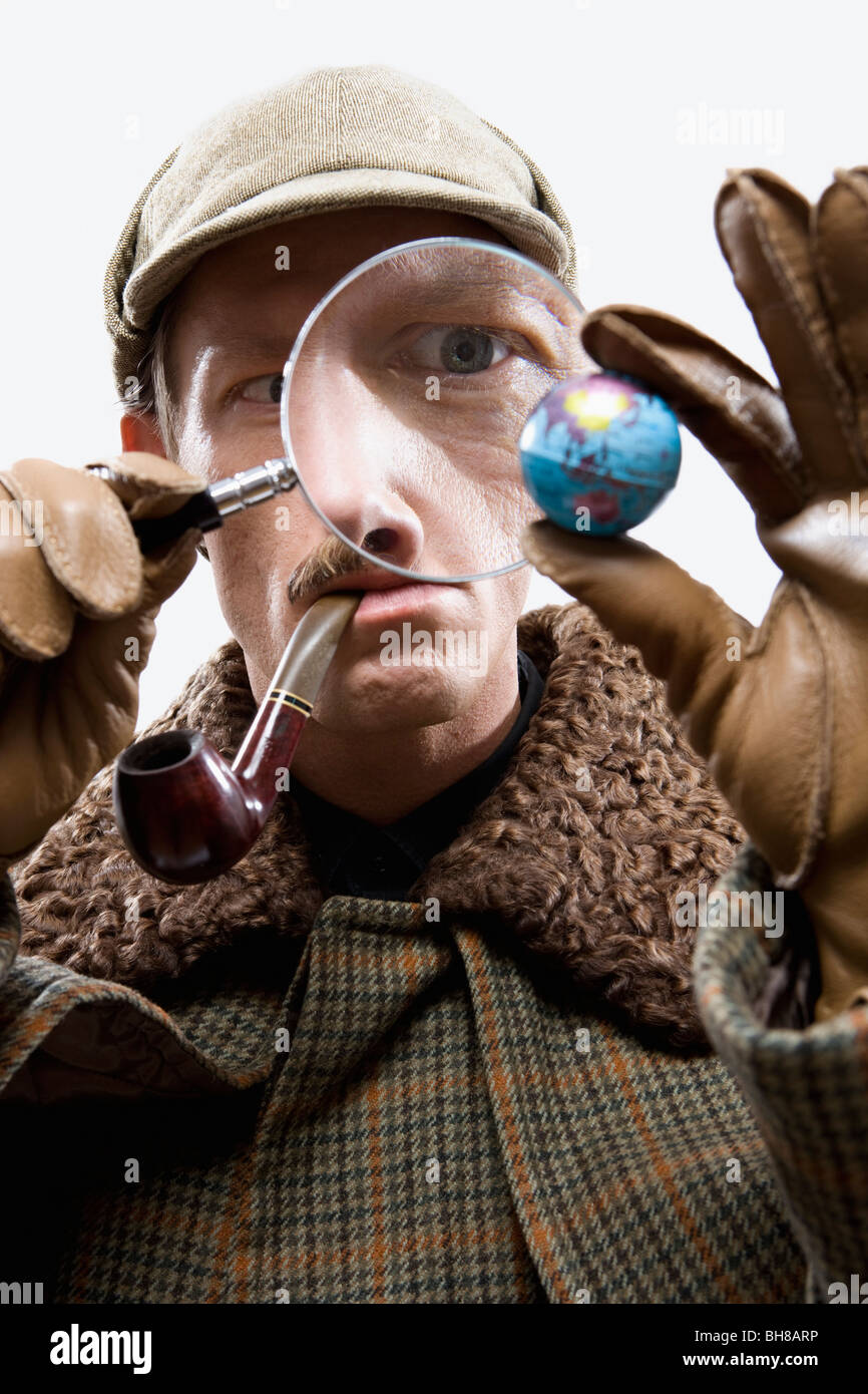 A man dressed up as Sherlock Holmes looking at a tiny globe through a magnifying glass - Stock Image