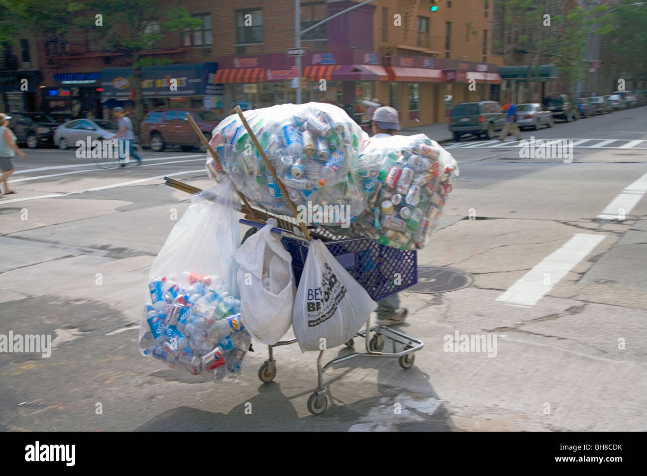 Man collects aluminum cans in grocery basket in upper Eastside of New York - Stock Image