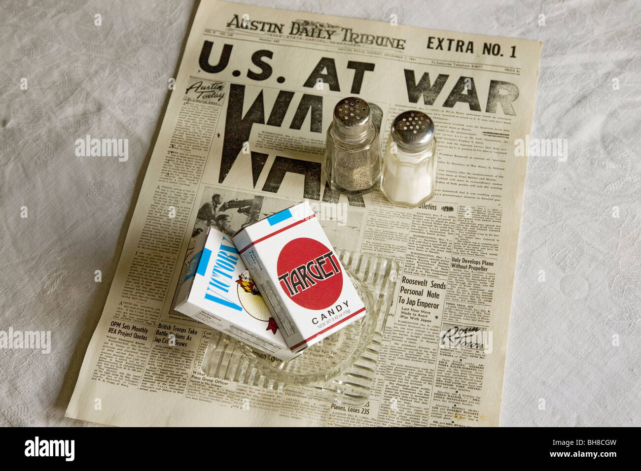 Still life of Austin Daily Tribune headline reading US AT WAR with Target candy cigarettes and salt and pepper shakers - Stock Image