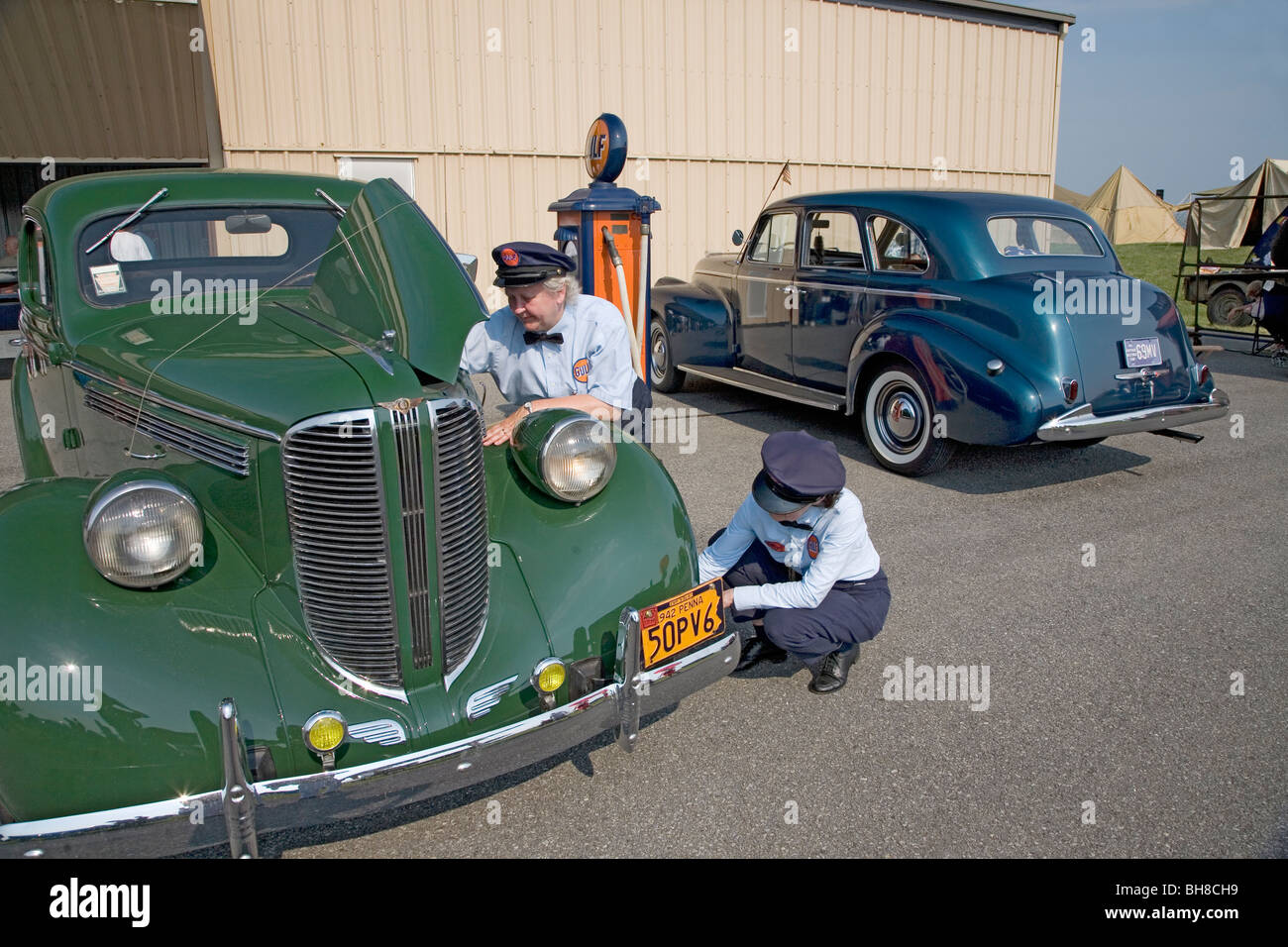 Reenactment of two women gas attendants servicing 1940s car during World War II at Mid-Atlantic Air Museum World - Stock Image