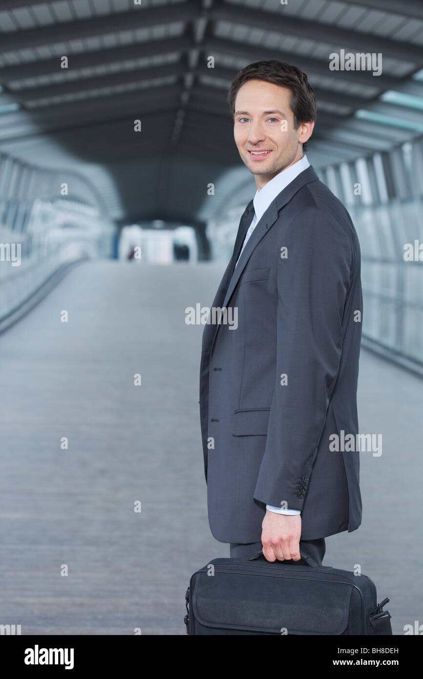 businessman with laptop case, happy - Stock Image
