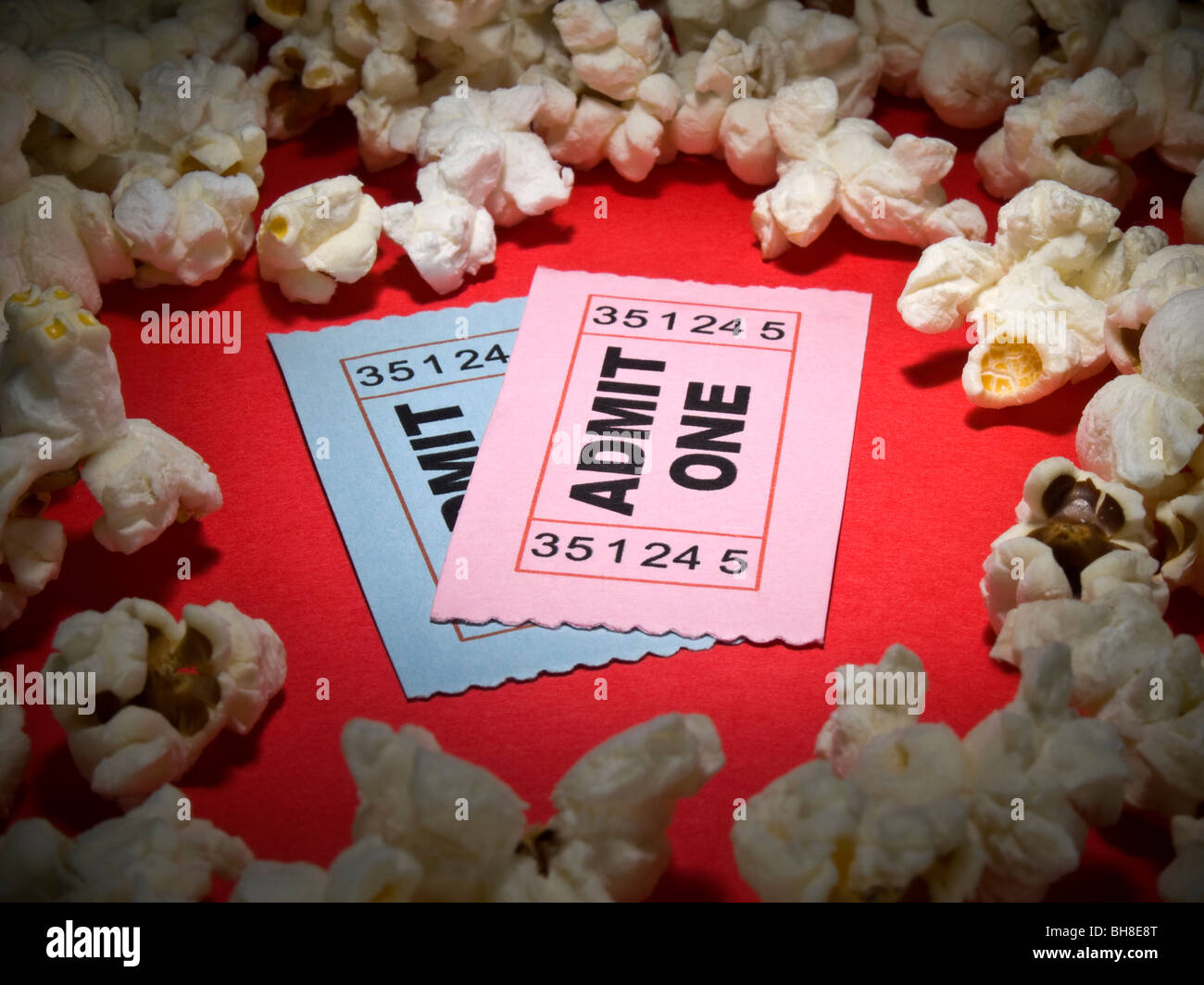 Close up shot of two generic admission tickets surrounded by popcorns. - Stock Image