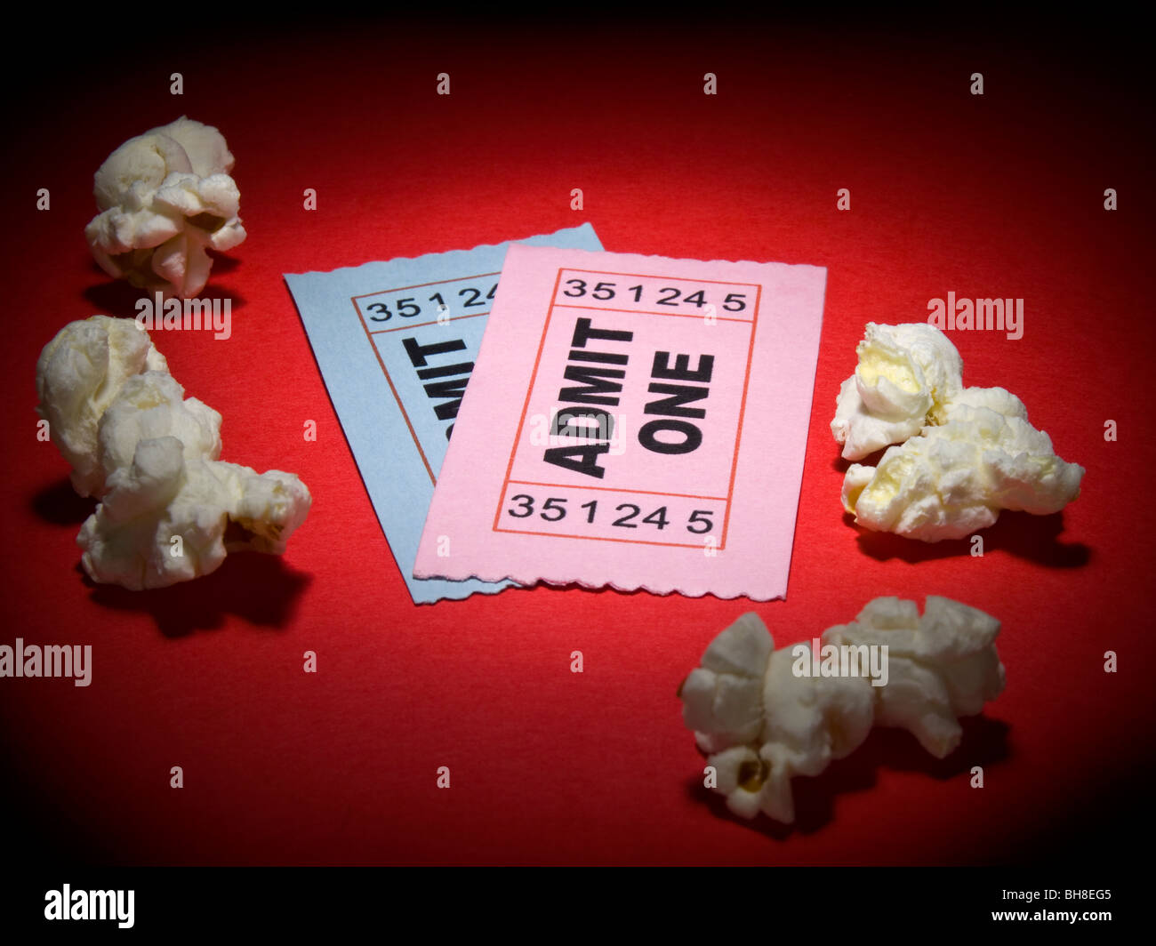 Close up shot of two generic admission tickets and some popcorns arround. - Stock Image