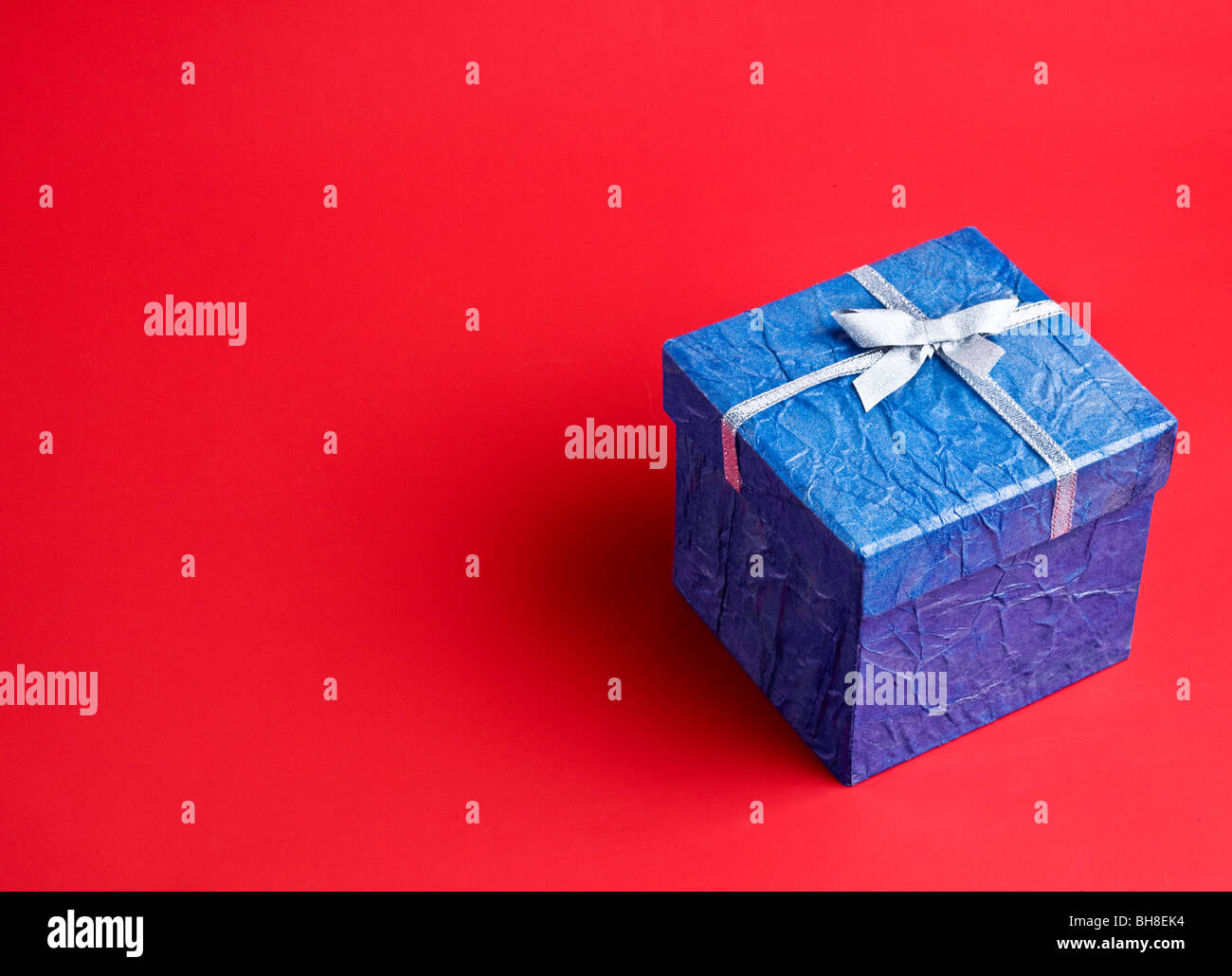 Blue gift on a red background - Stock Image