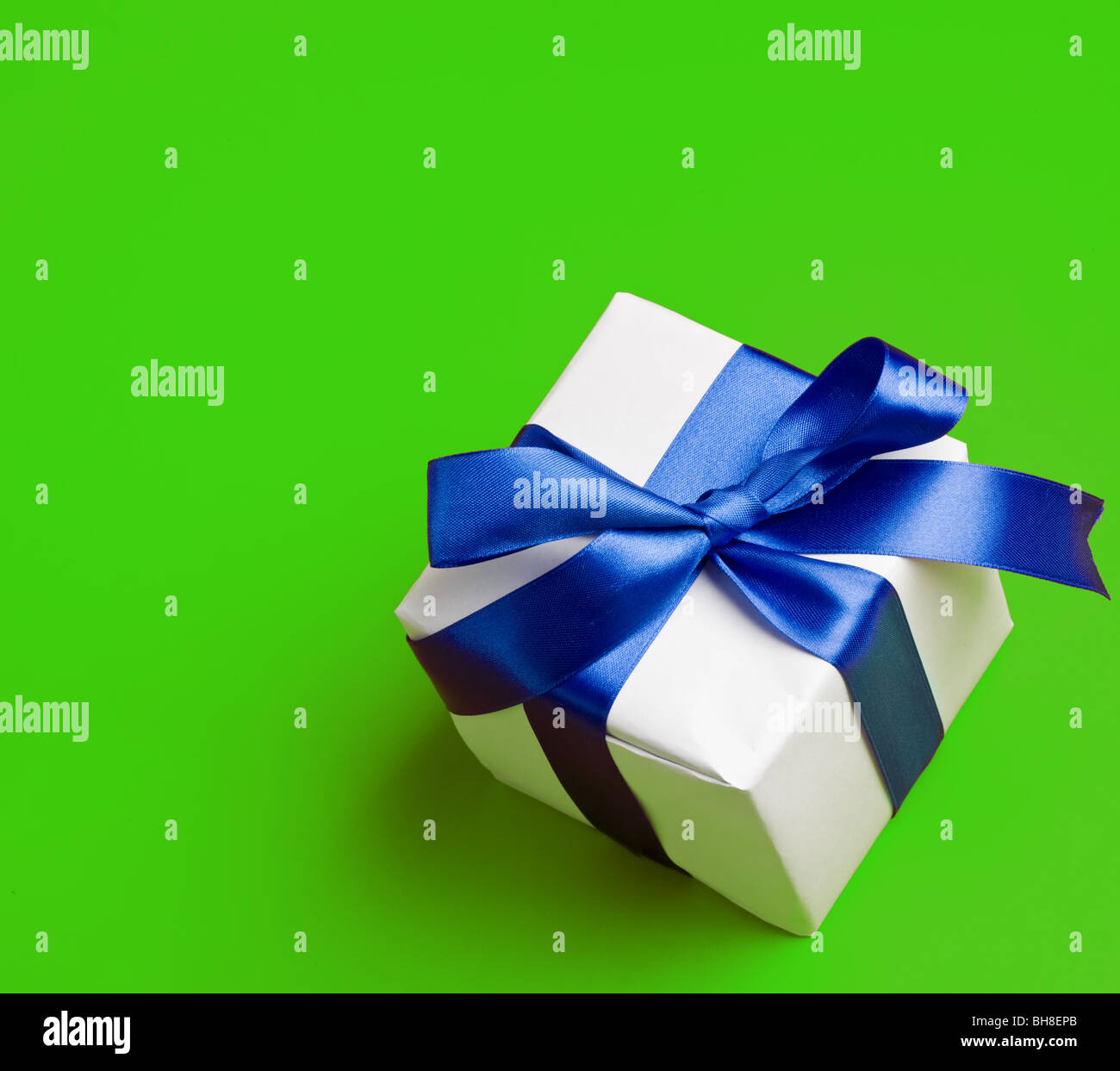 white gift in a blue ribbon on a green background - Stock Image