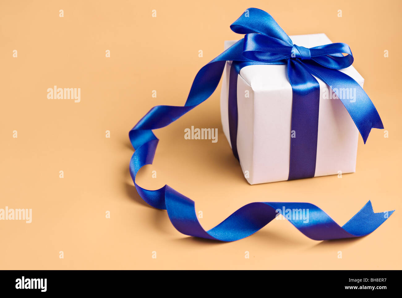 white gift with blue ribbon on a biege background - Stock Image