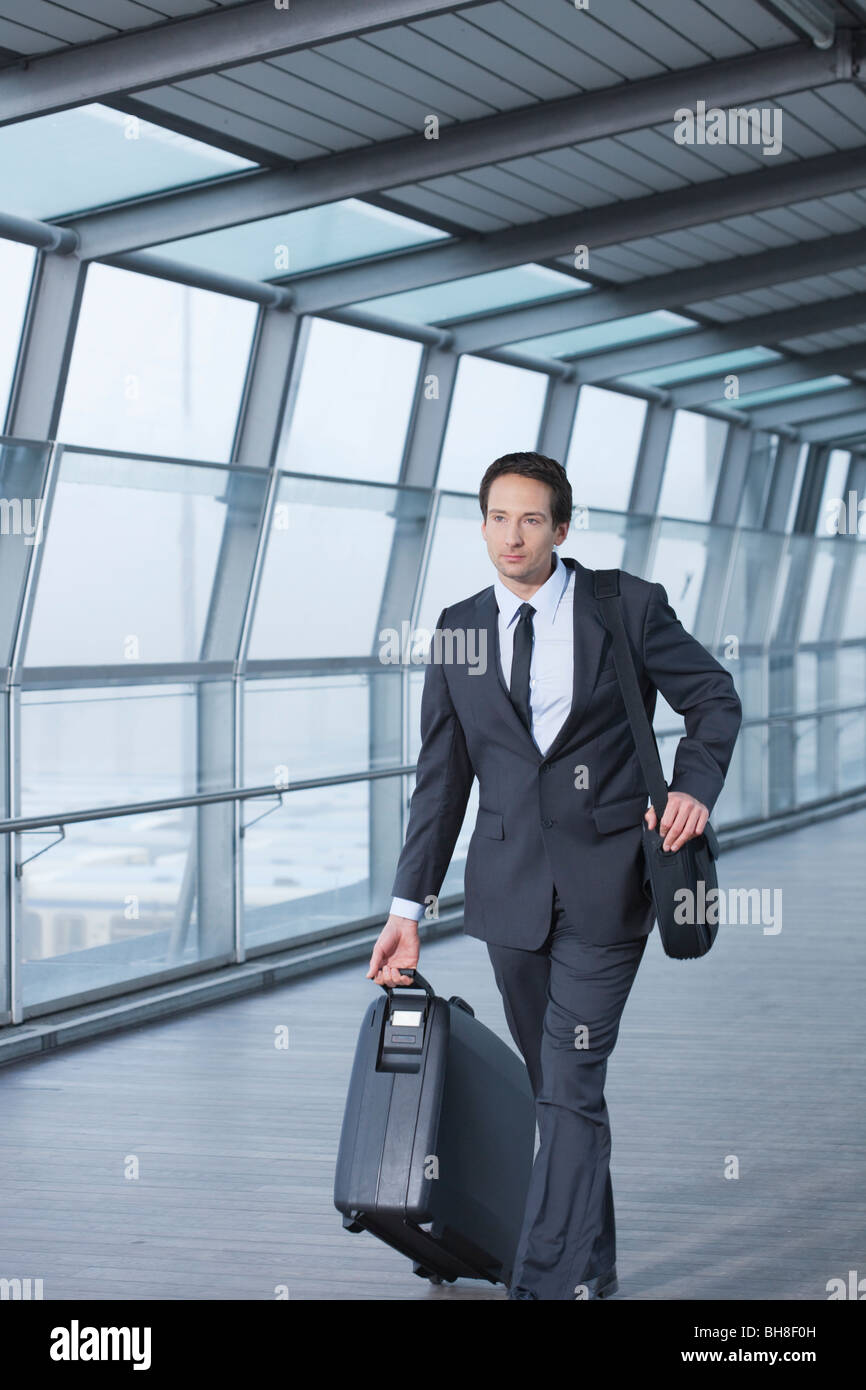 businessman with case walking in skywalk - Stock Image