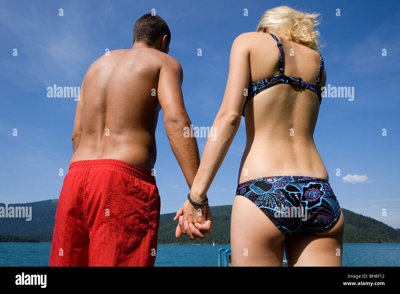 A couple holding hands by a lake - Stock Image