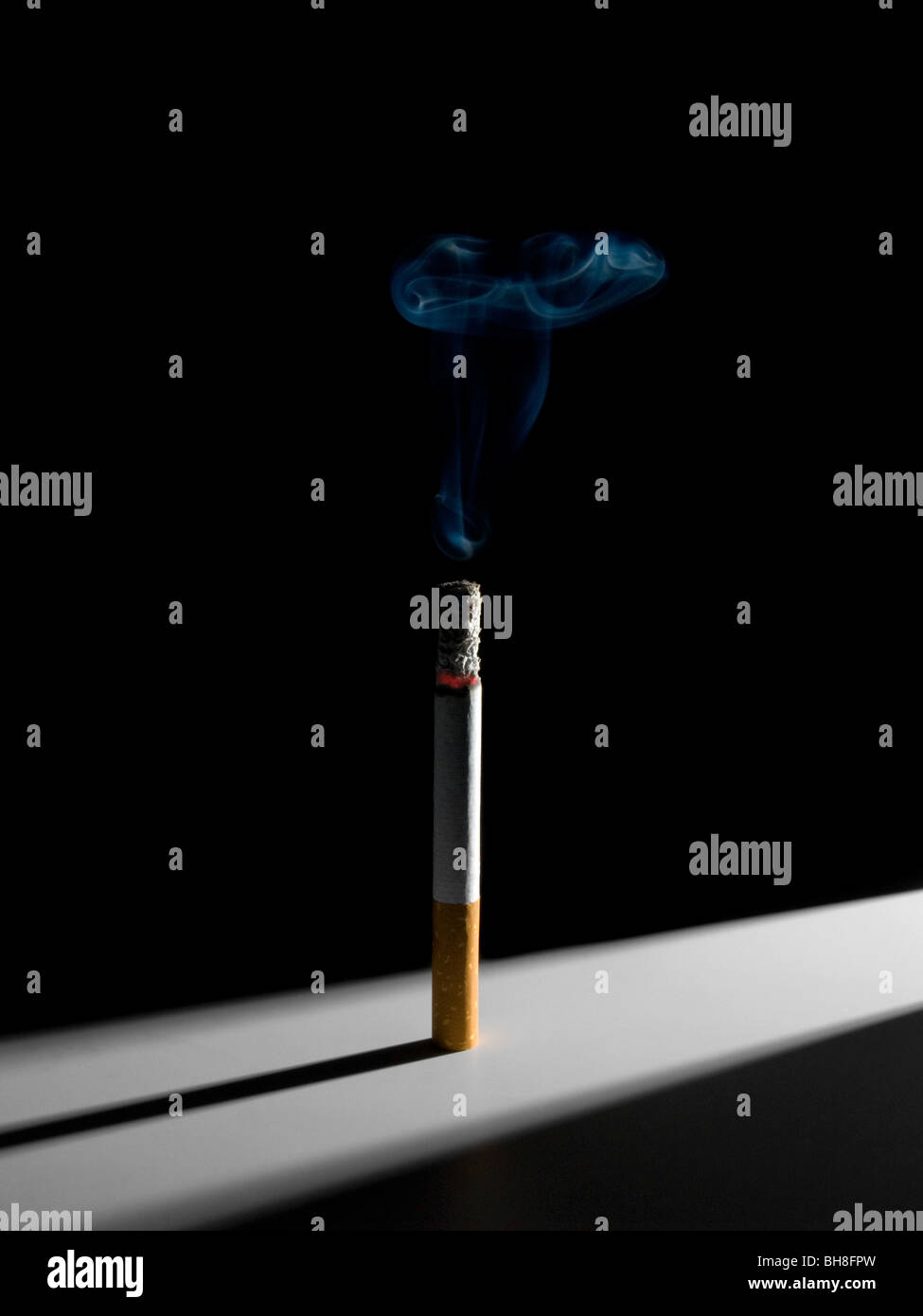 A single smoking cigarette standing in a narrow corridor of light. A conceptual image about the smoking habit. - Stock Image