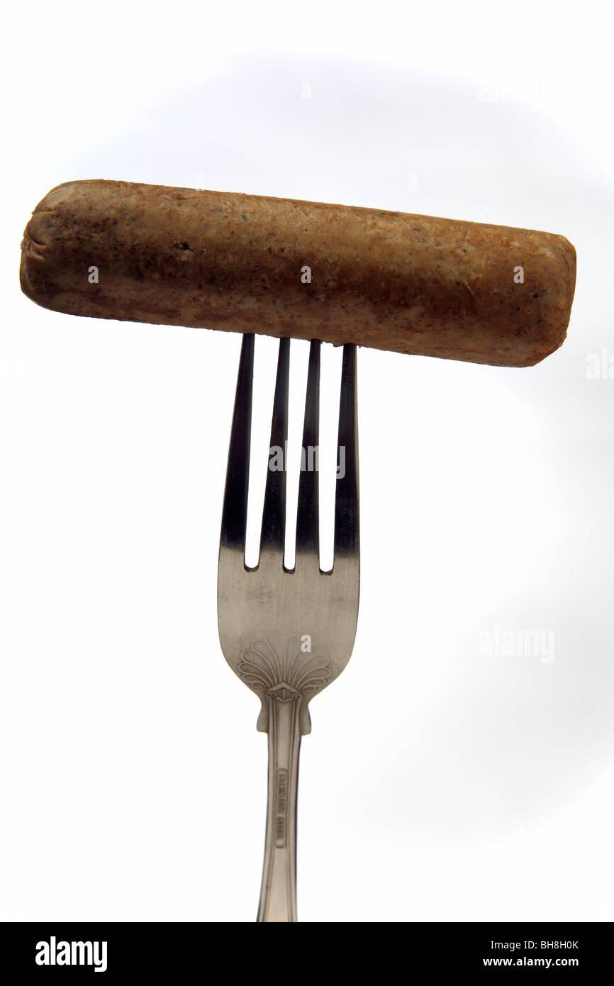 Vegetarian sausage on a fork. - Stock Image