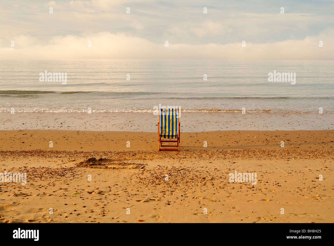 View of the sandy beach and abandoned striped wooden deckchair at Bournemouth in Dorset in south west England UK - Stock Image