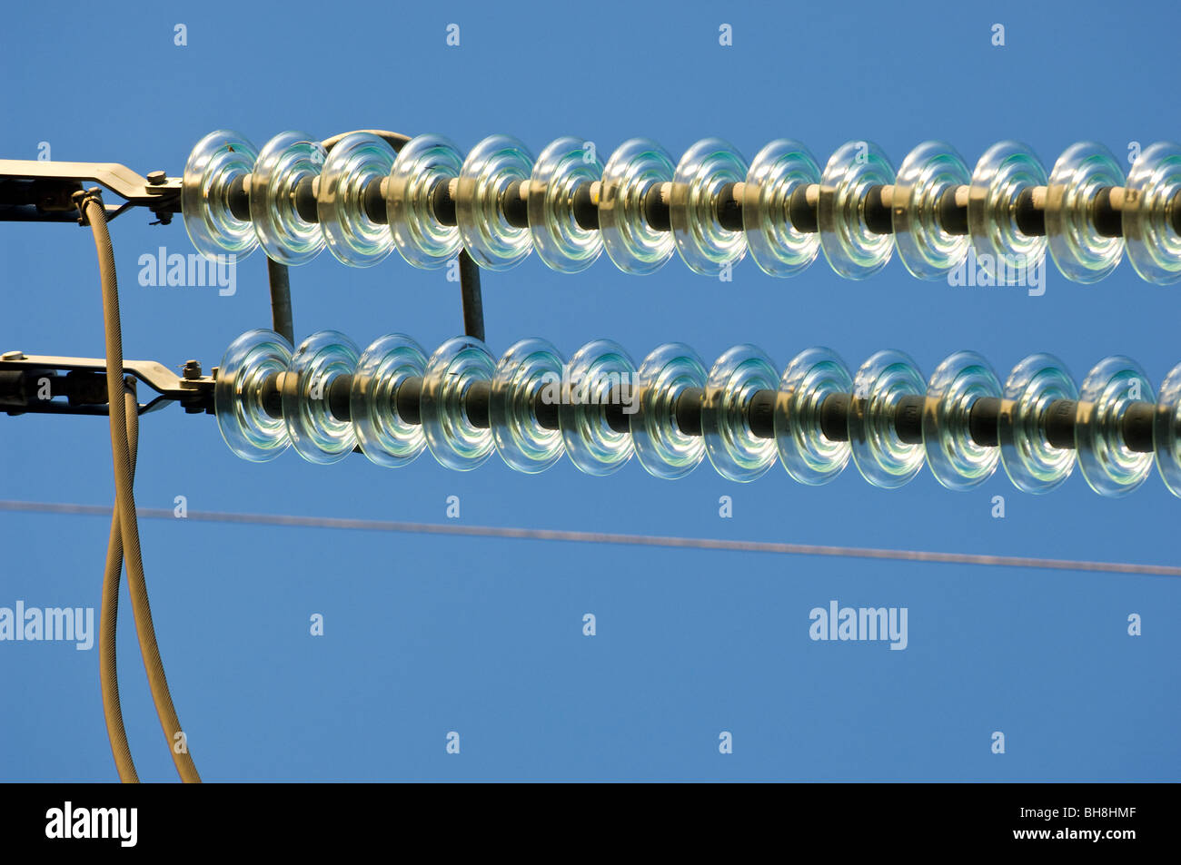 High voltage overhead cables transmission lines operating at 275kV with glass insulators. - Stock Image