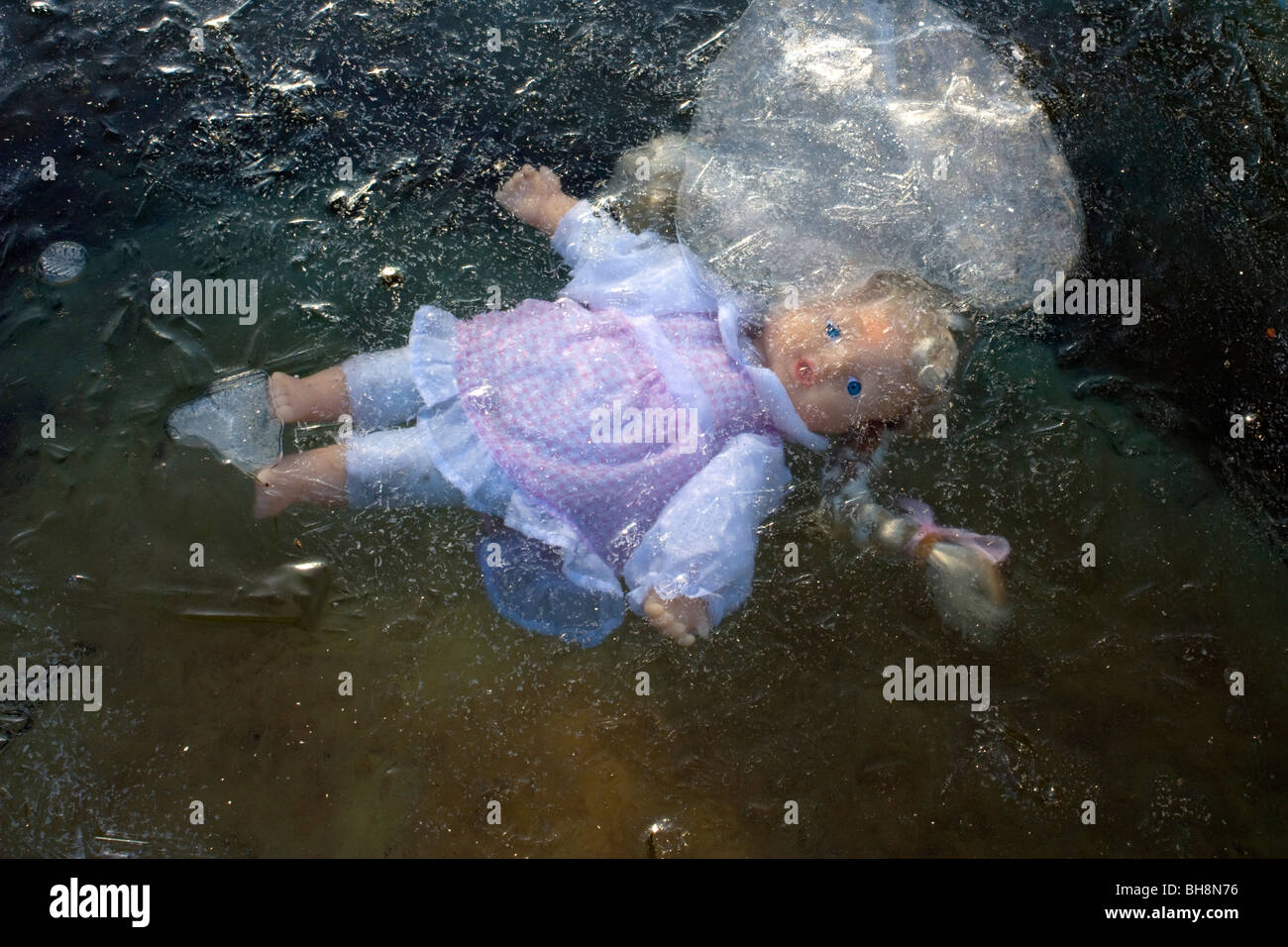 Doll trapped under ice - Stock Image