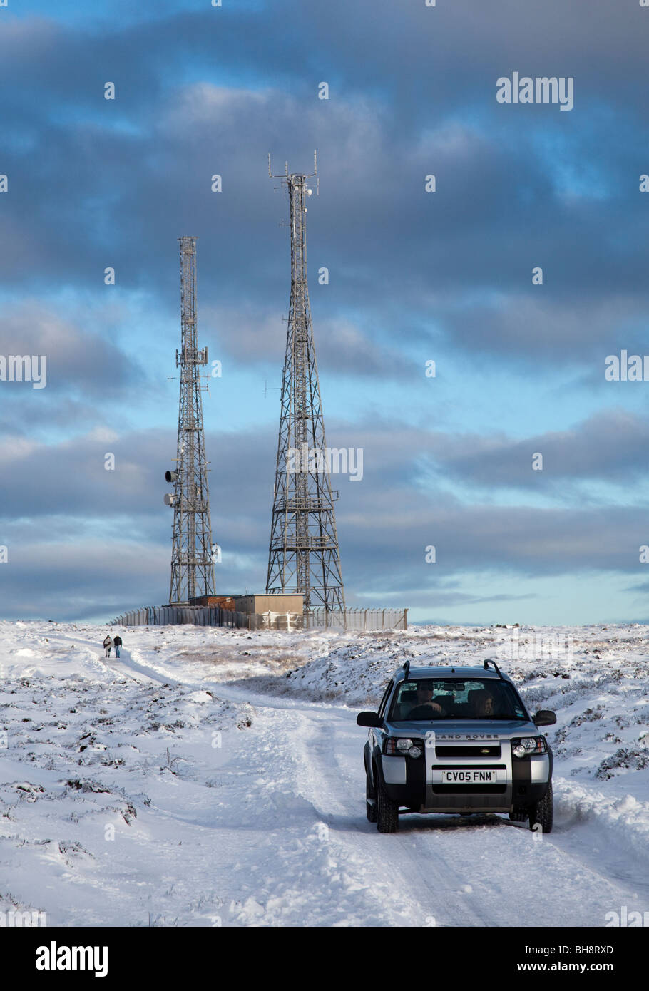 Land Rover vehicle on snowy road on moorland with aerial masts in winter Blorenge Wales UK - Stock Image