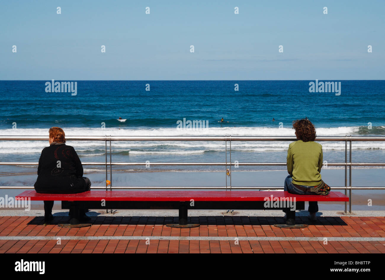 Young slim woman and large elderly lady sitting on bench looking out to  sea. -