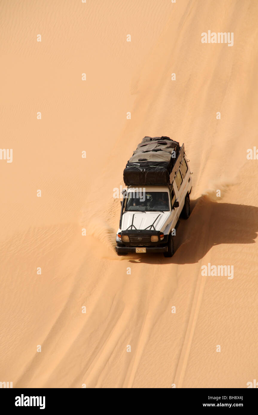 A desert safari land cruiser 4x4 jeep crests a giant sand dune in the Great Sand Sea of the Western Desert, Egyptian - Stock Image