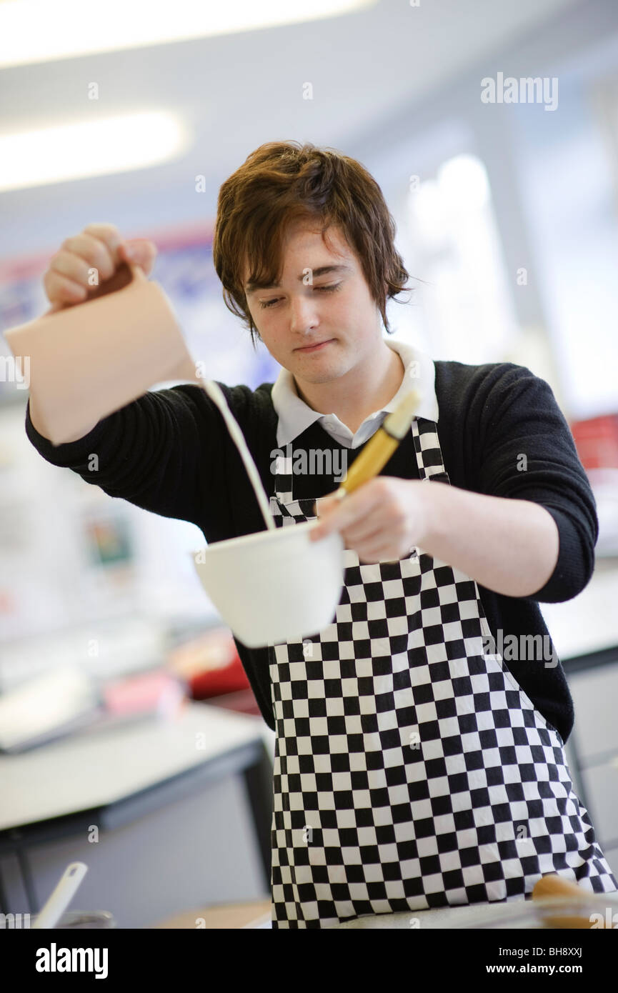 Teenage boy measuring ingredients and pouring milk into a bowl in food science cookery class , secondary school - Stock Image