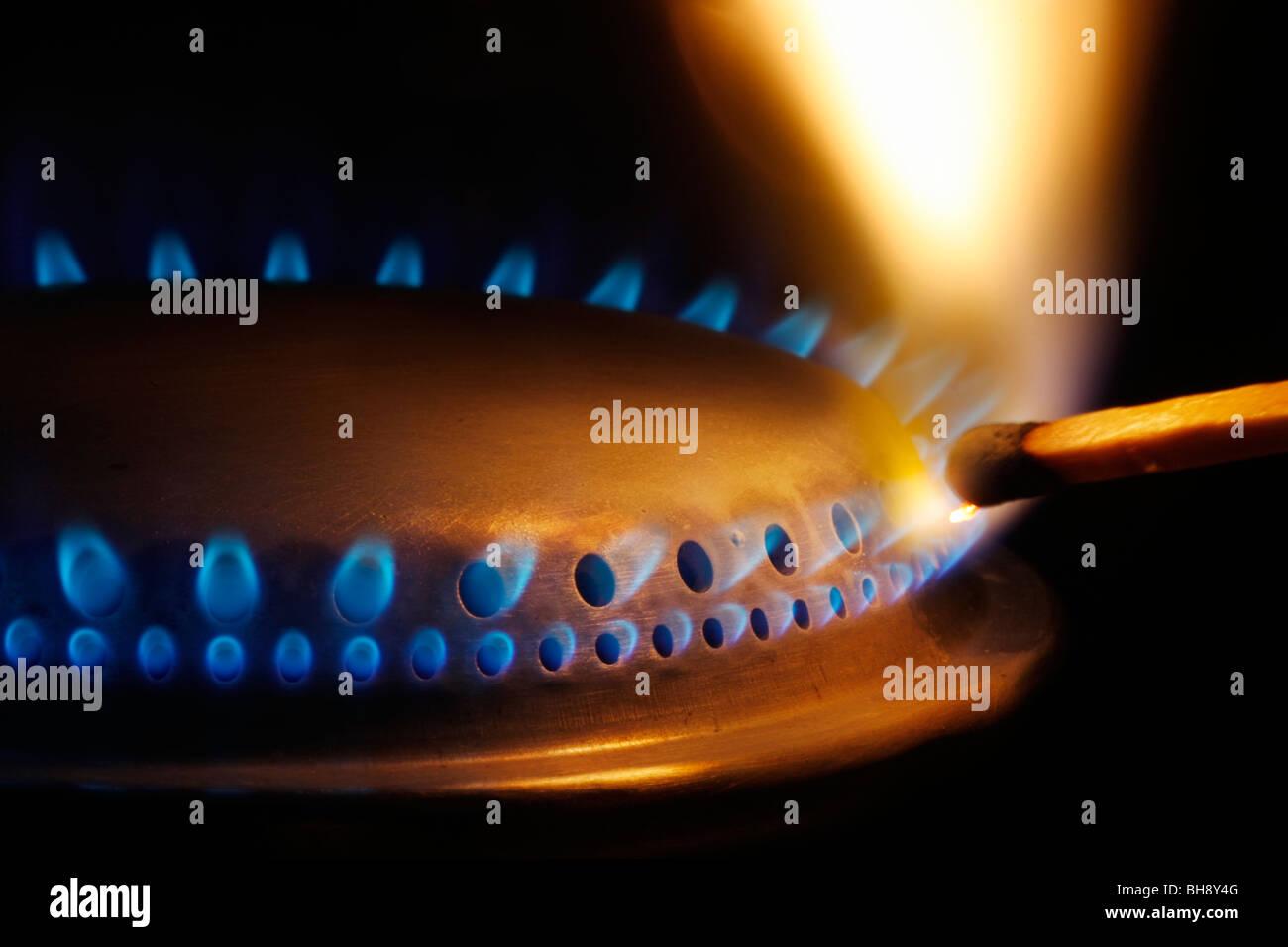 Close-up of a match lightening a gas burner - Stock Image
