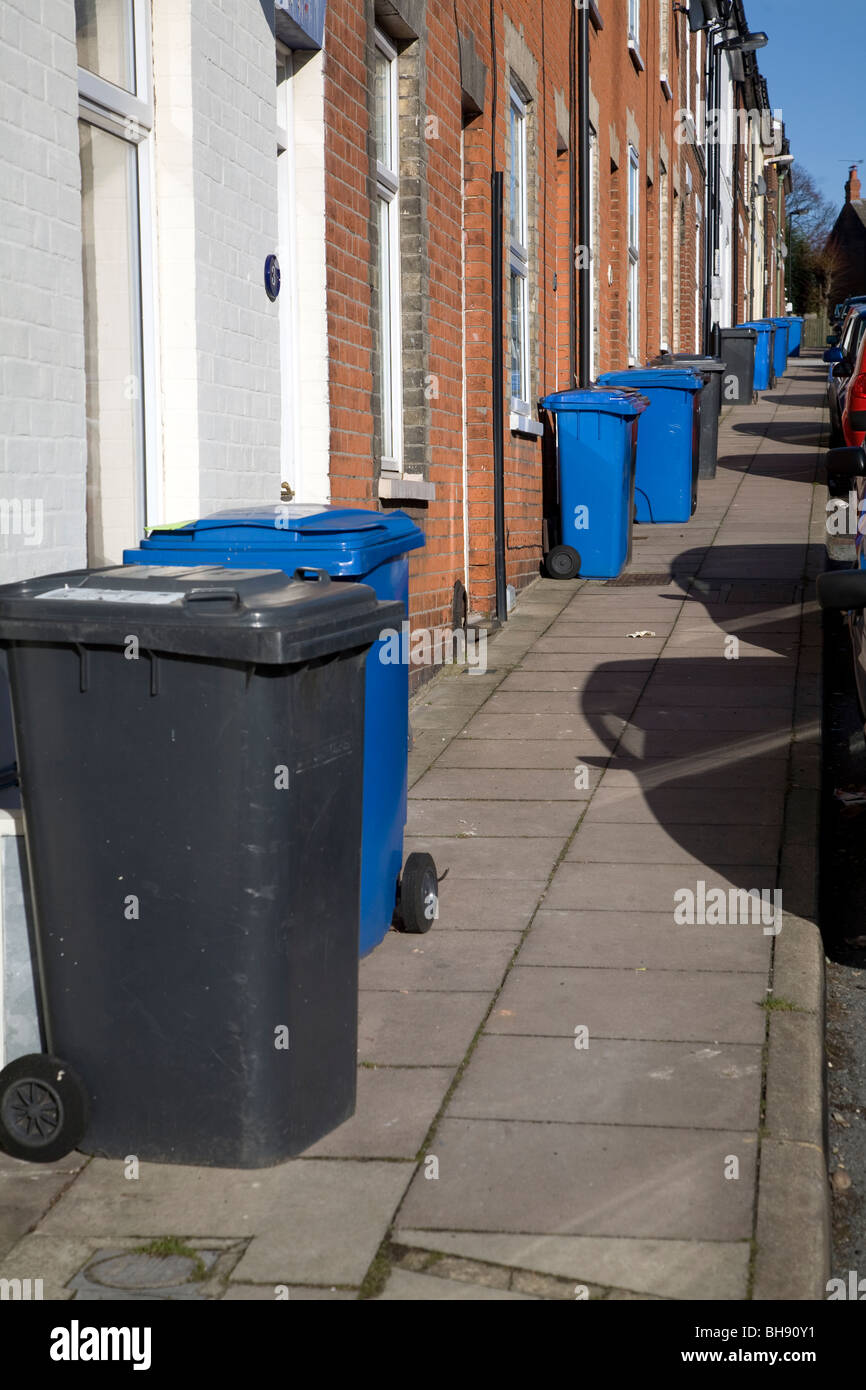 Refuse and recycling rubbish bins on pavement outside terraced housing - Stock Image