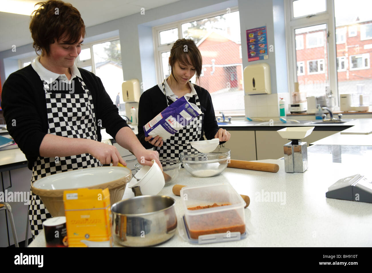 Two teenagers pupils - boy and girl measuring ingredients in food science cookery class , secondary school UK - Stock Image