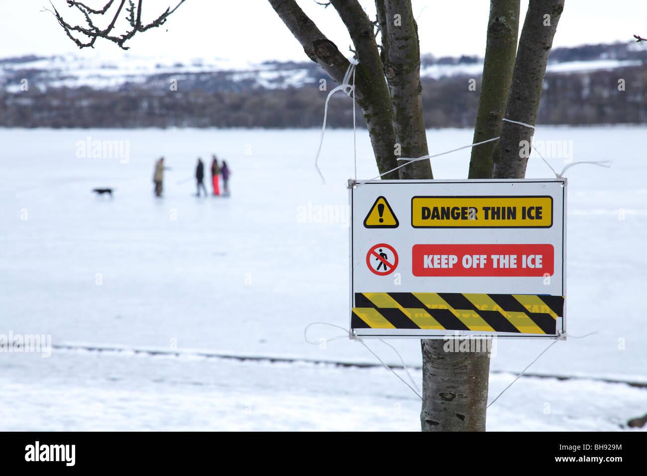 People on frozen Castle Semple Loch beside Thin Ice Warning sign, Muirshiel Regional Park, Lochwinnoch, Renfrewshire - Stock Image