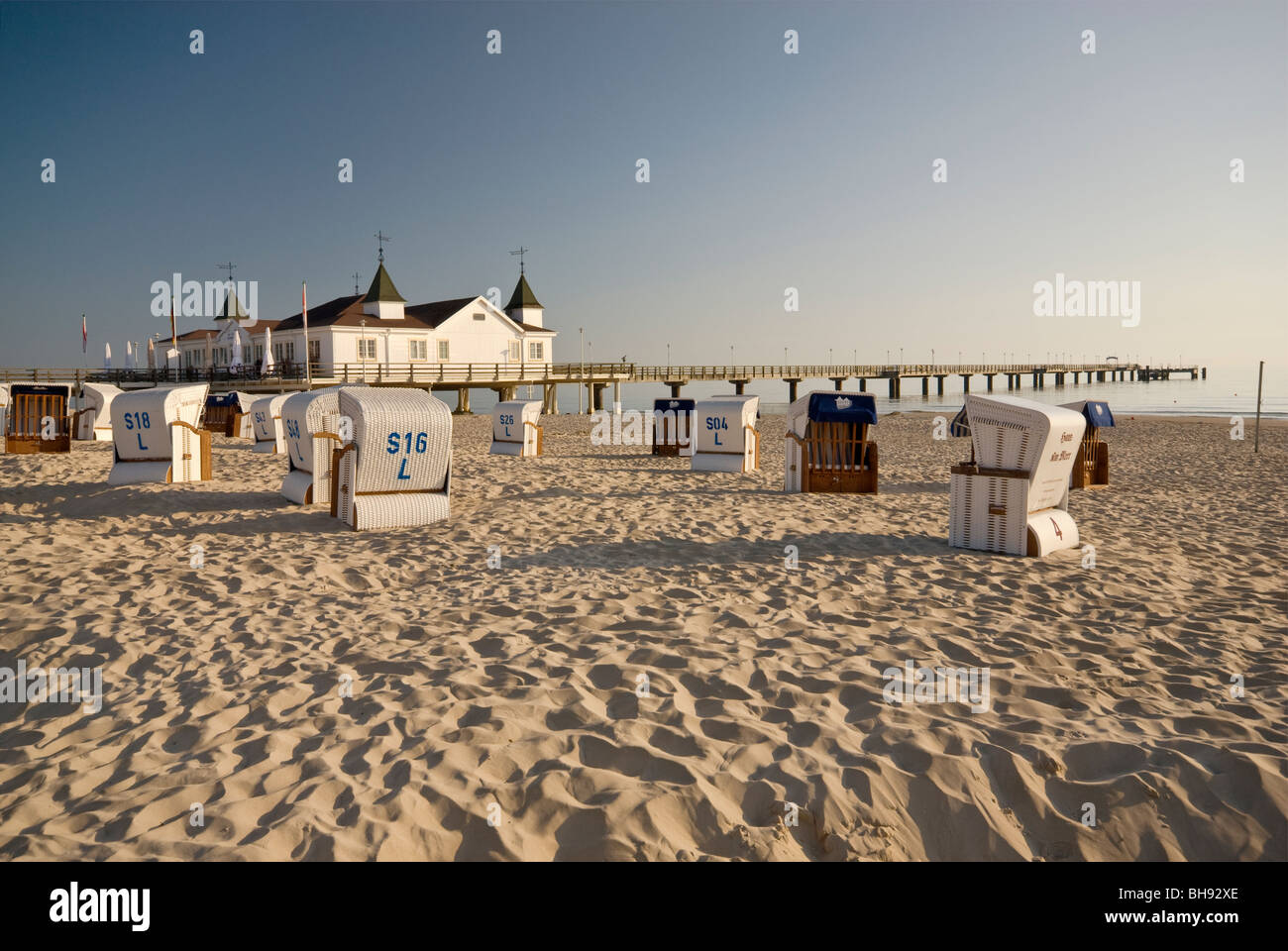 Wicker beach chairs and Seebrücke pier in Ahlbeck at Usedom Island in Mecklenburg-West Pomerania, Germany - Stock Image