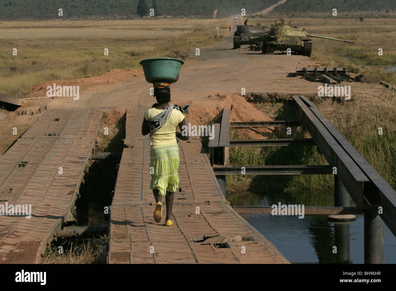 Angolan woman carrying basket on her head walks towards two tanks which were abandoned at Longa, Angola, Africa. - Stock Image