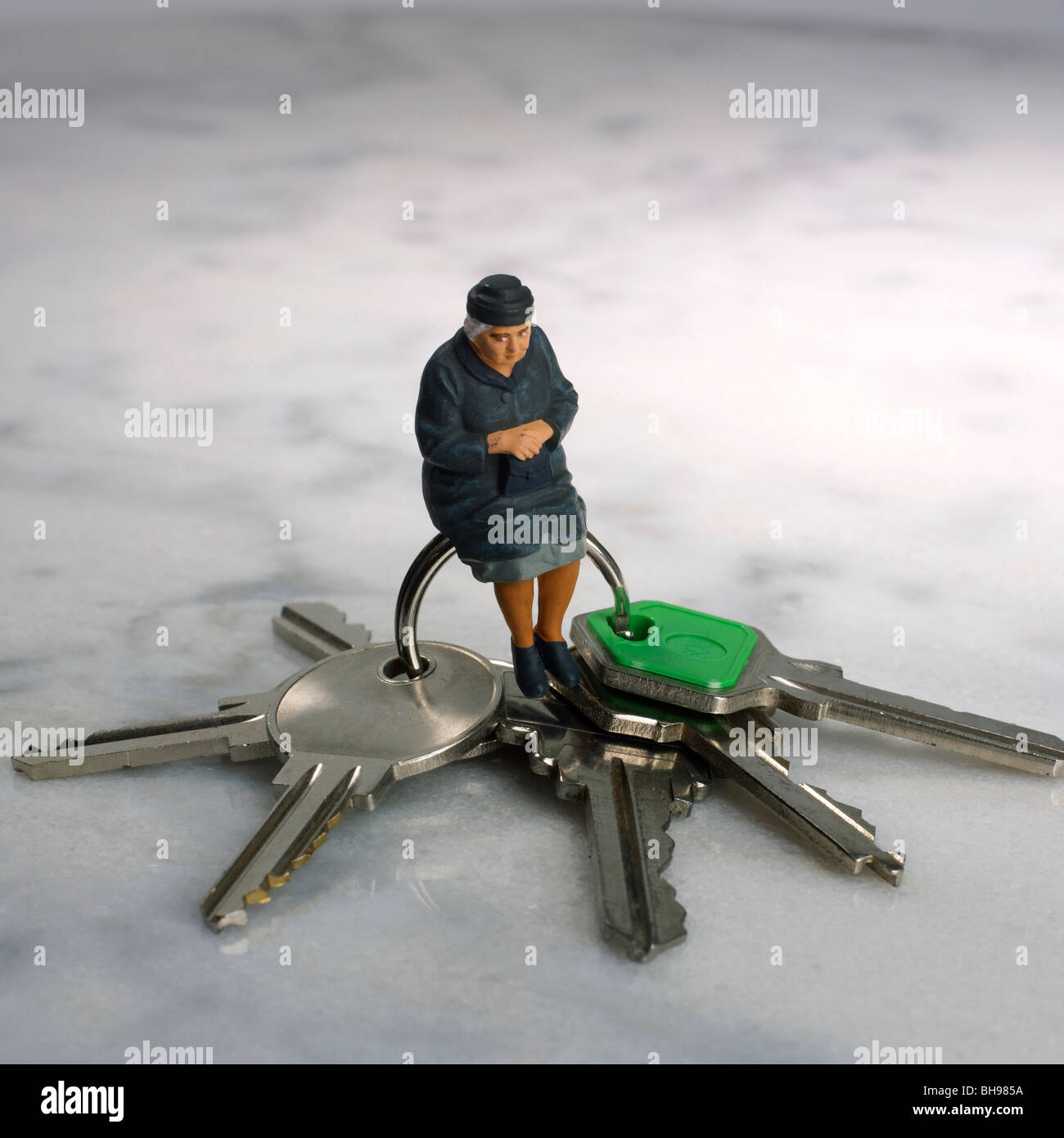 Old woman, figurine, and keys - housing / retirement concept - Stock Image