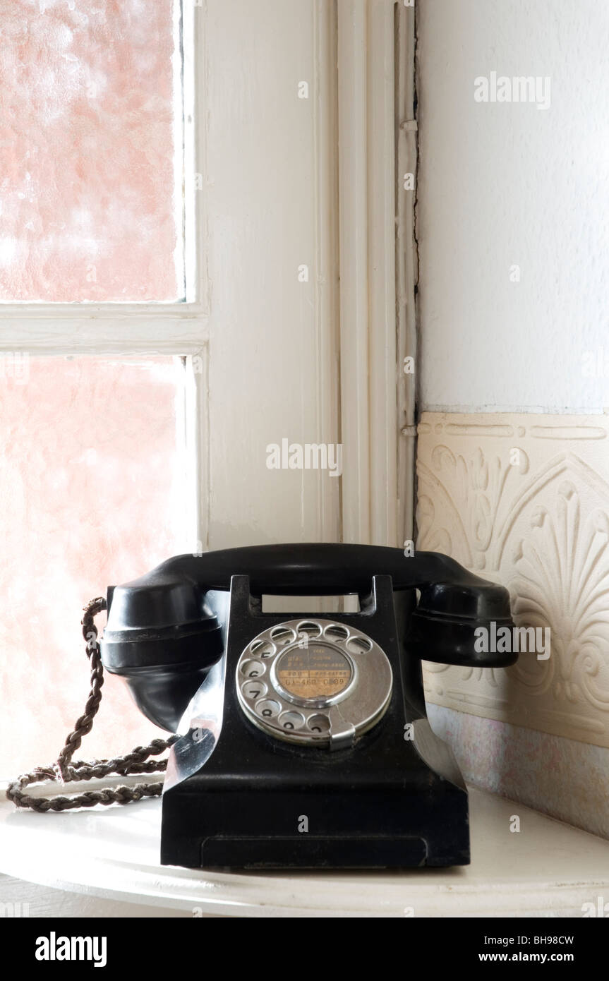An old-fashioned Bakelite telephone sitting on a corner table in a house. - Stock Image