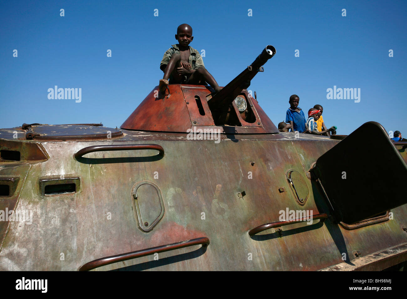 Children play on an old tank on a former battle field at Cuito Cuanavale, South Eastern Angola, Africa. - Stock Image
