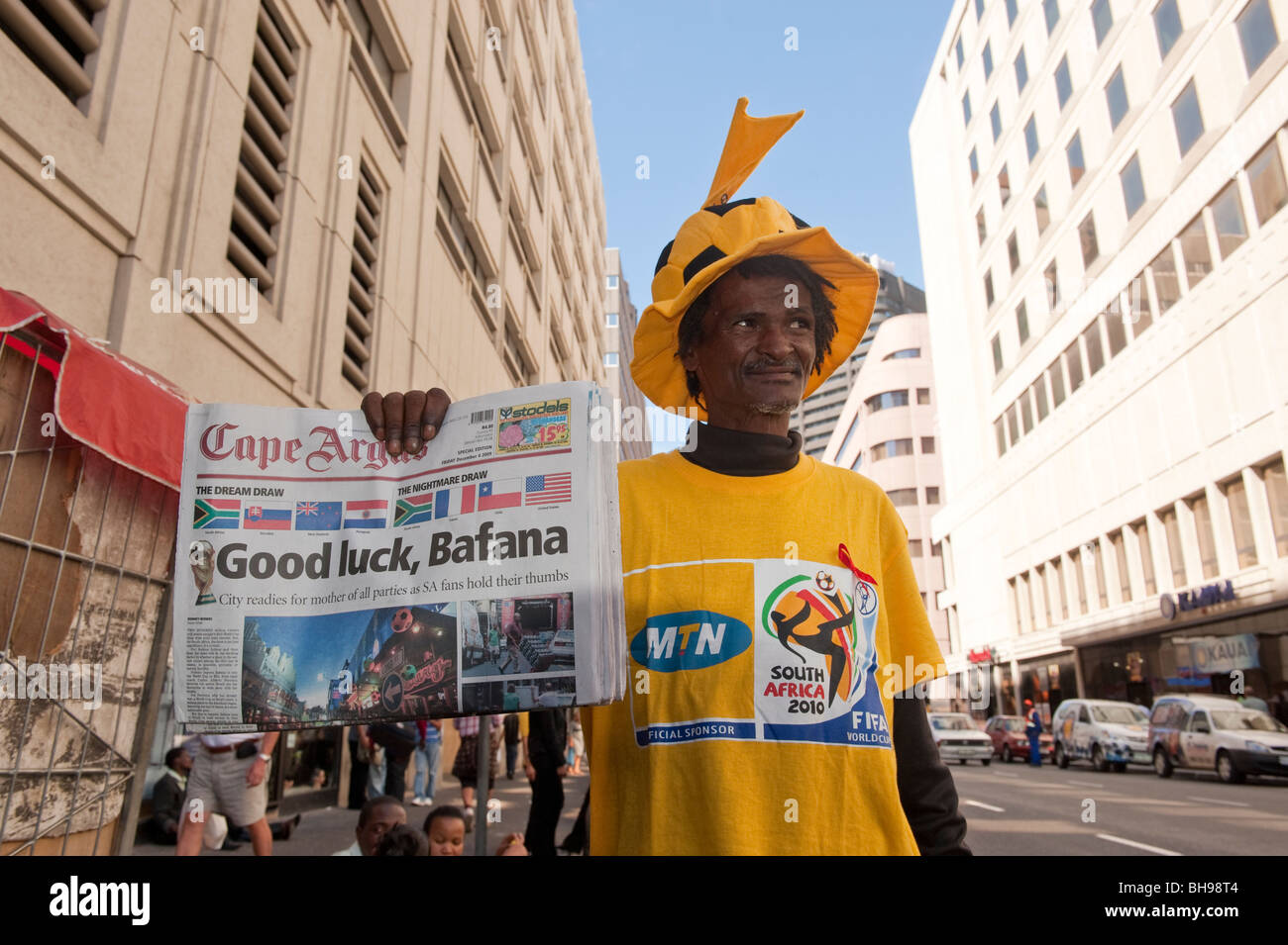 Newsman selling newspaper with headline about Bafana Bafana the African National football team Cape Town South Africa - Stock Image