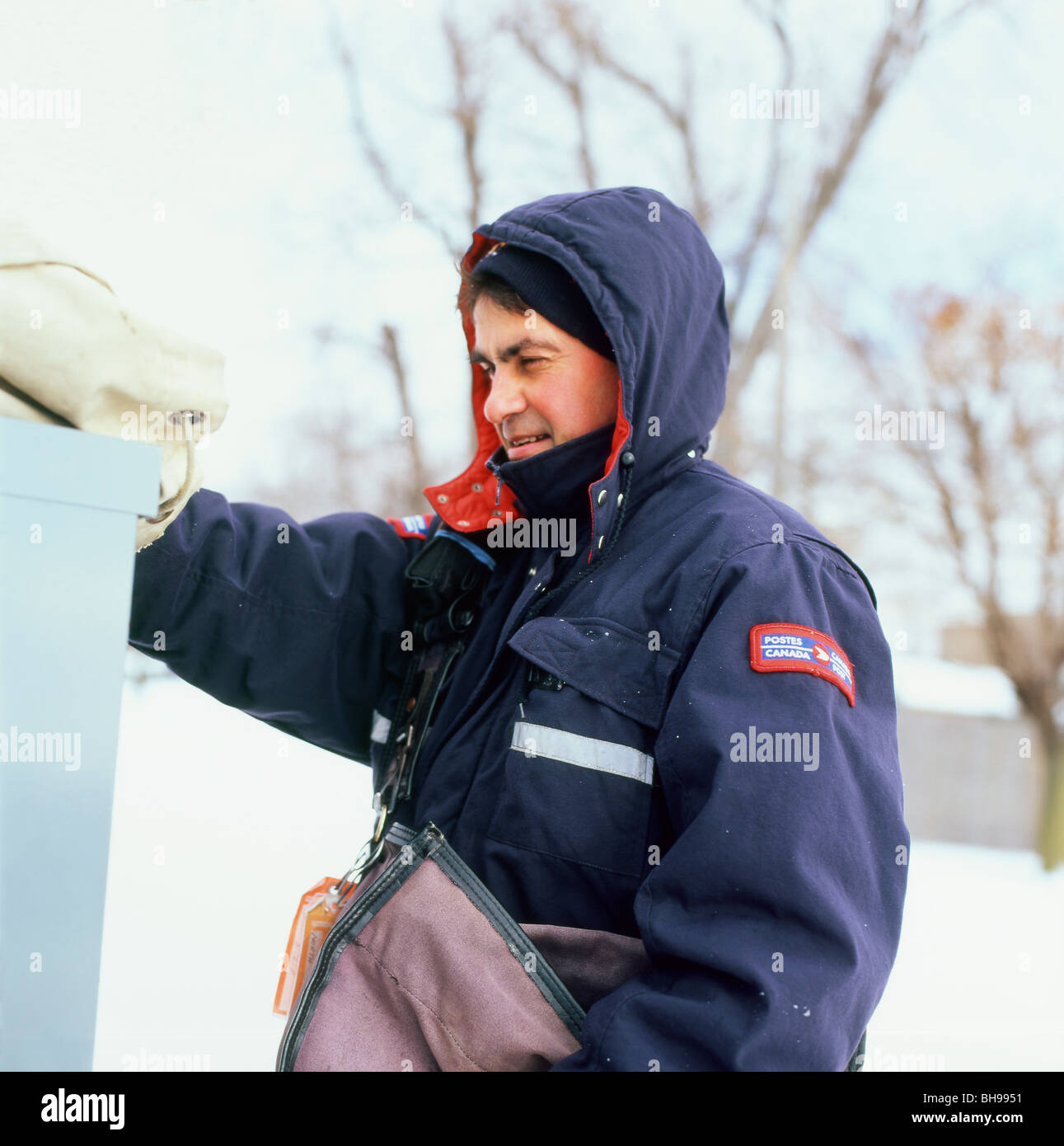 Postman with postal bag at work in winter clothing delivering letters in the snow Ontario Canada KATHY DEWITT - Stock Image