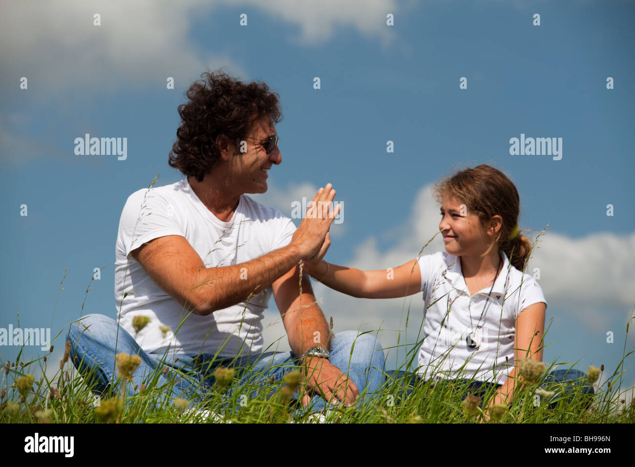 Father and daughter touching hands - Stock Image