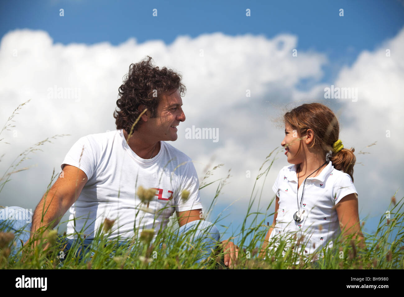 Father and daughter smiling at eachother seated in the grass in a summer day - Stock Image