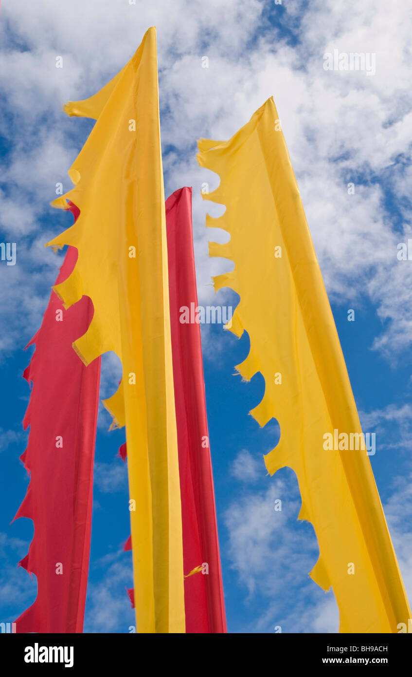 Yellow and red flags fluttering in the sunshine at Hay Festival 2009. - Stock Image