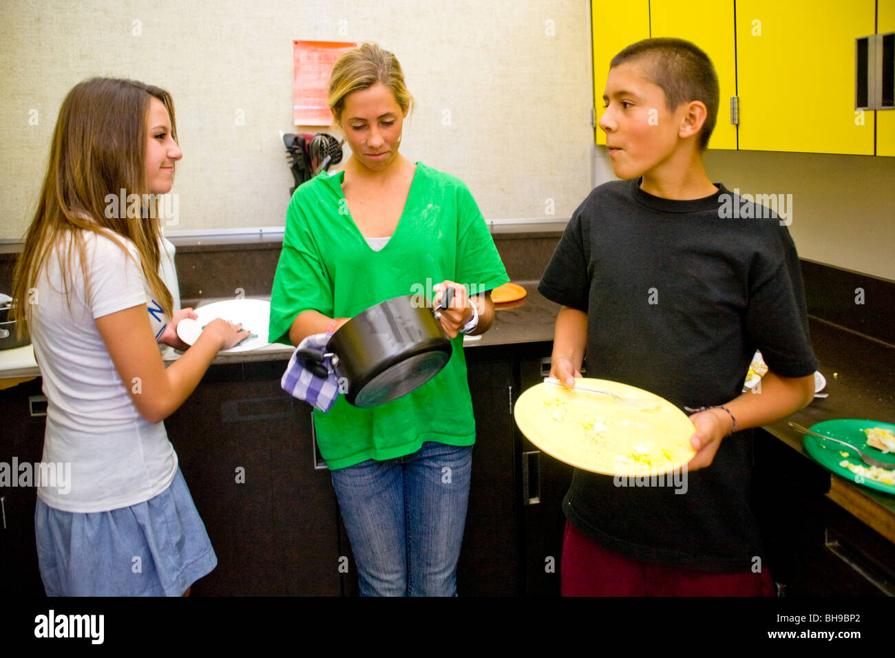 Eighth-grade boys and girls at a Southern California middle school clean up their kitchen area after a cooking lesson. - Stock Image