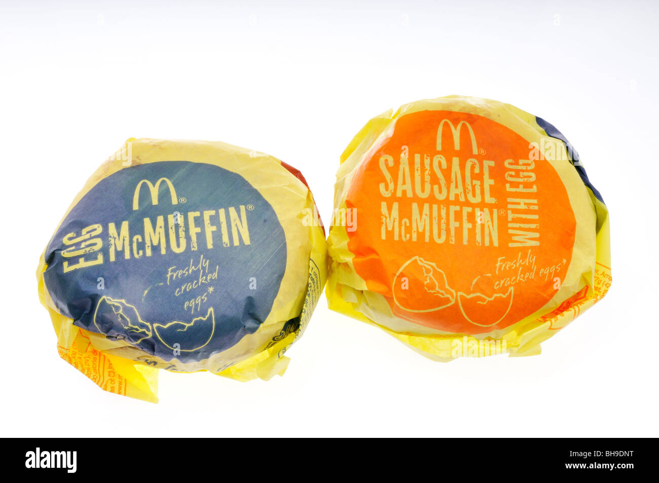 McDonald's Egg McMuffin and sausage McMuffin breakfast sandwiches in wrappers on white background. Cut out - Stock Image