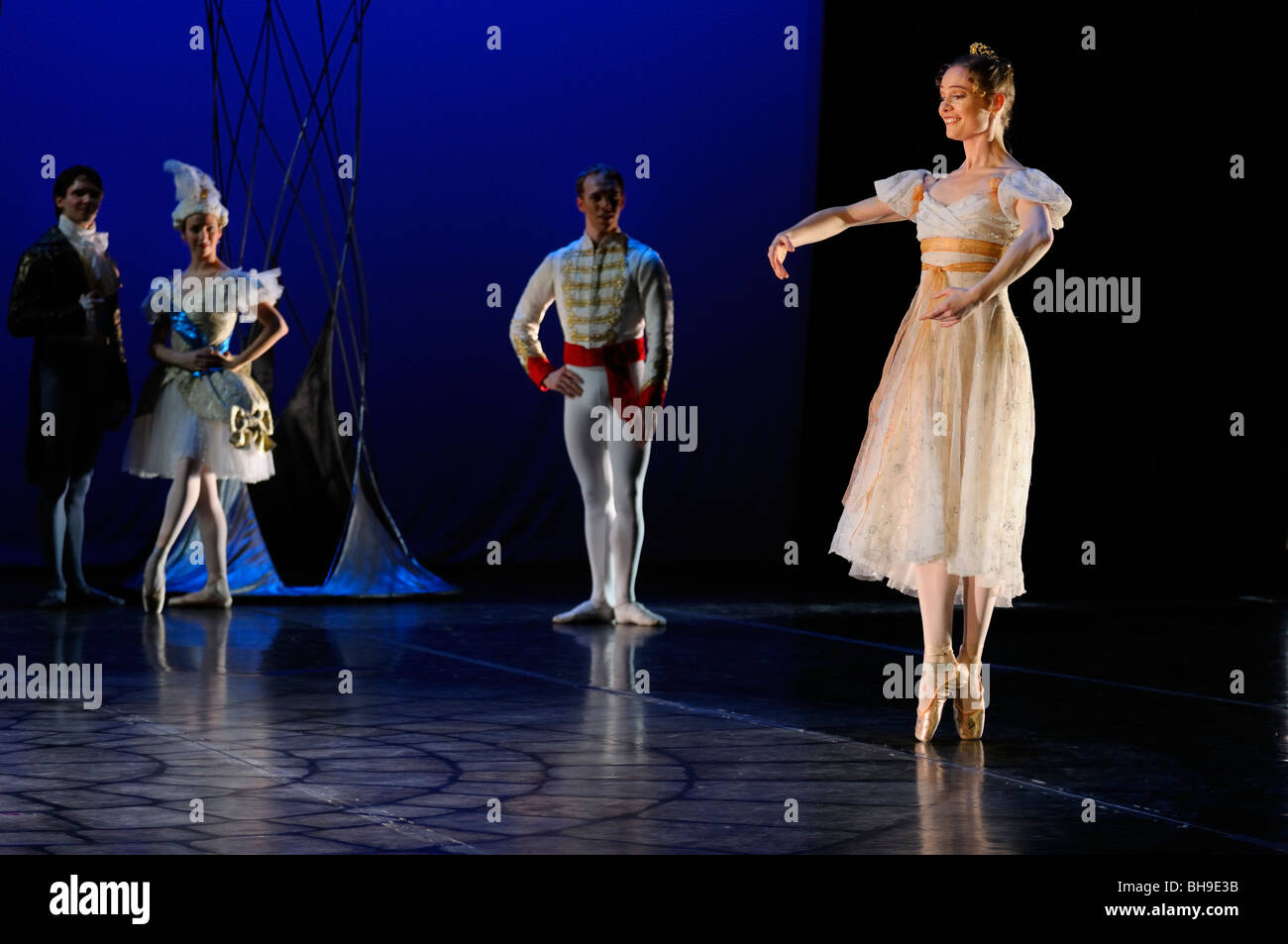 Cinderella dancing solo en pointe at the Ball while Prince Charming looks on in Ballet Jorgen stage production - Stock Image