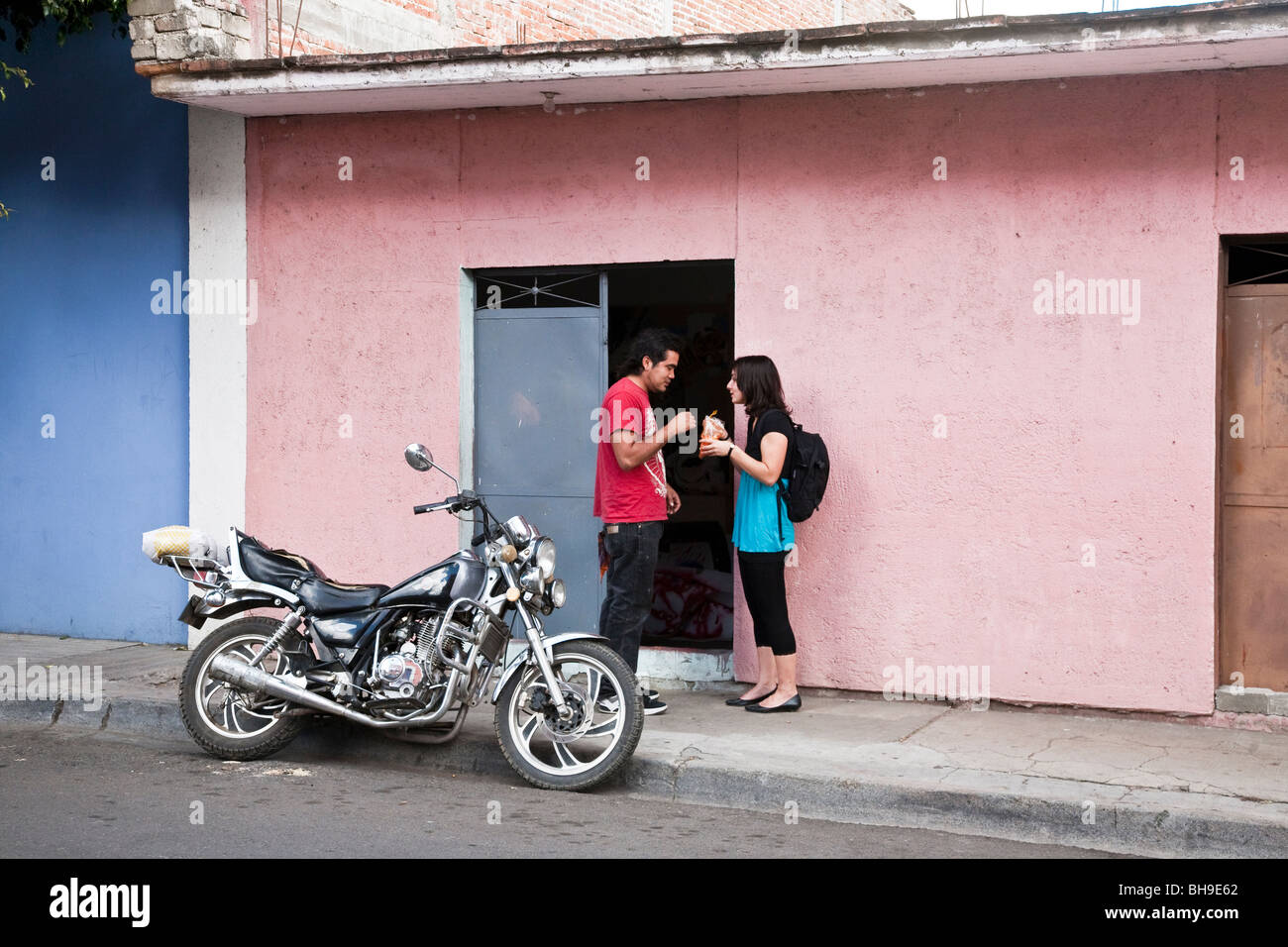 boy & girl sharing a treat on Oaxaca City street accompanied by splendid motorbike against a backdrop of pink - Stock Image