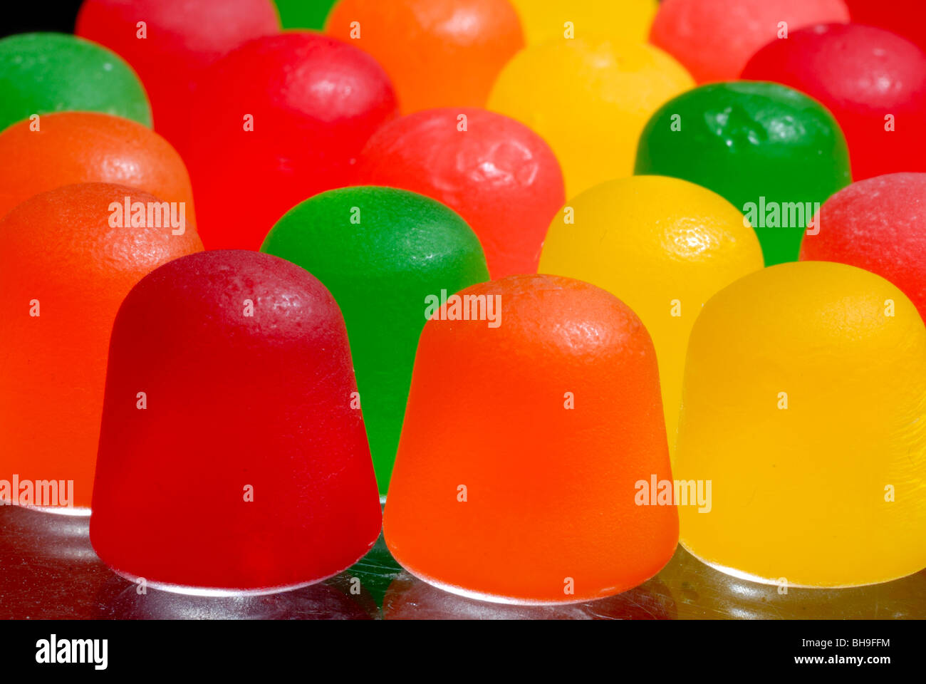 A macro shot of colorful gumdrop candies. - Stock Image