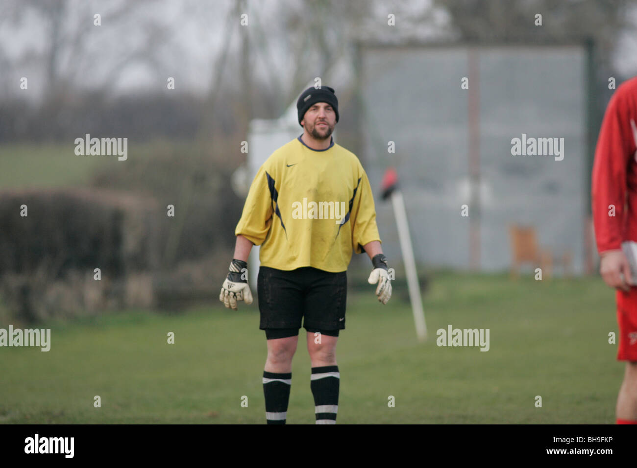 A goalkeeper playing local league football (soccer) keeps warm by wearing a woolen hat. - Stock Image